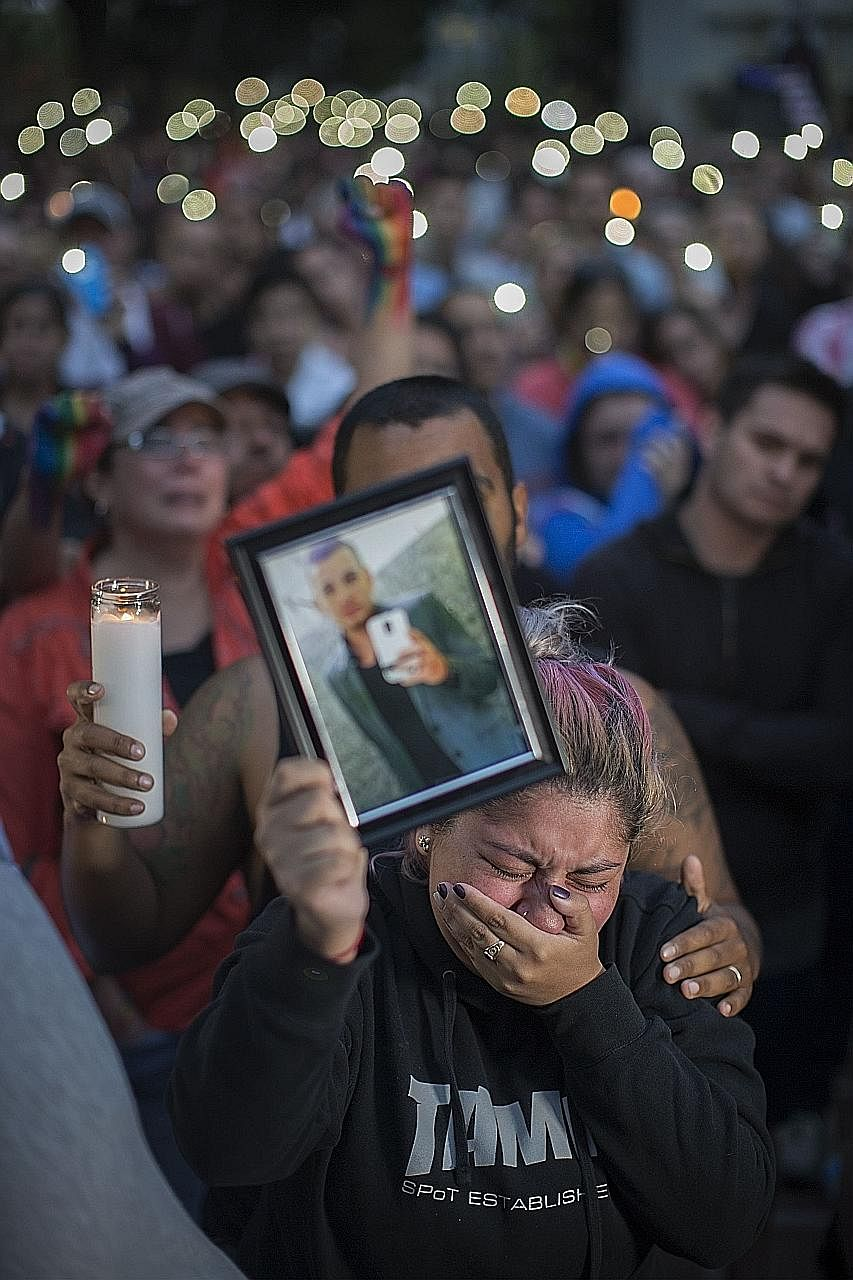 Ms Alison Cosio displaying a photo of her friend Christopher Sanfeliz during a vigil on Monday in Los Angeles. He was among those killed at the Pulse nightclub in Orlando on Sunday in the worst mass shooting in US history.