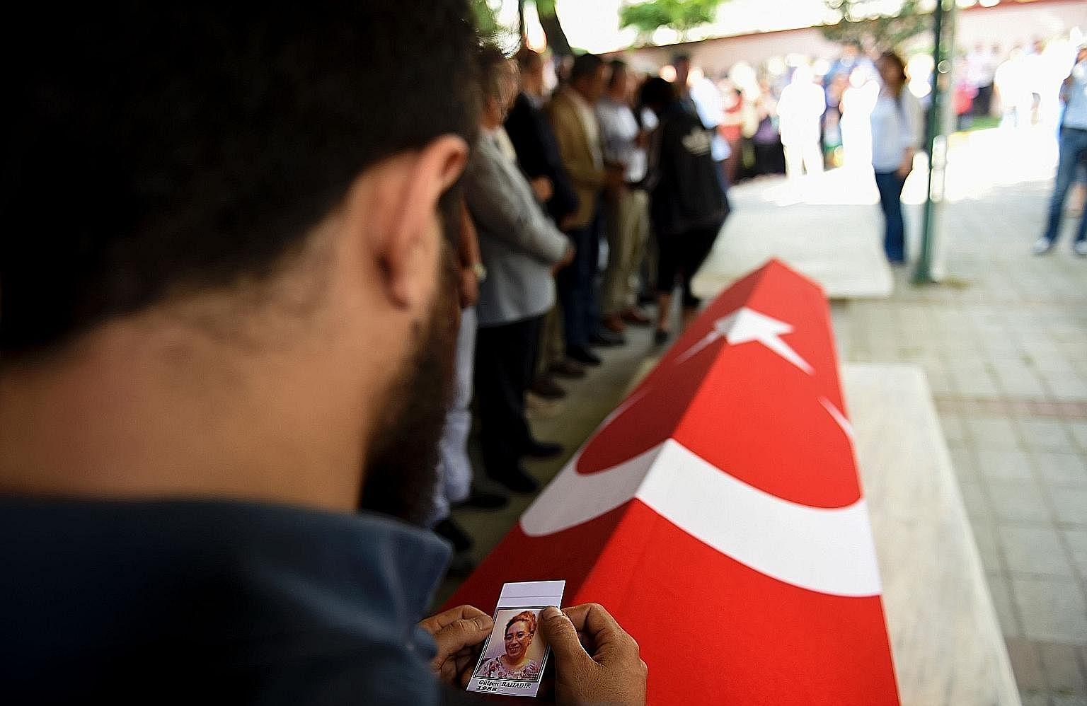 A friend of air hostess Gulsen Bahadir, who was killed during Tuesday night's attacks on Ataturk airport, with her photo next to the coffin during the funeral in Istanbul. The assault on the airport is the latest in a series of horrible traumas in Tu