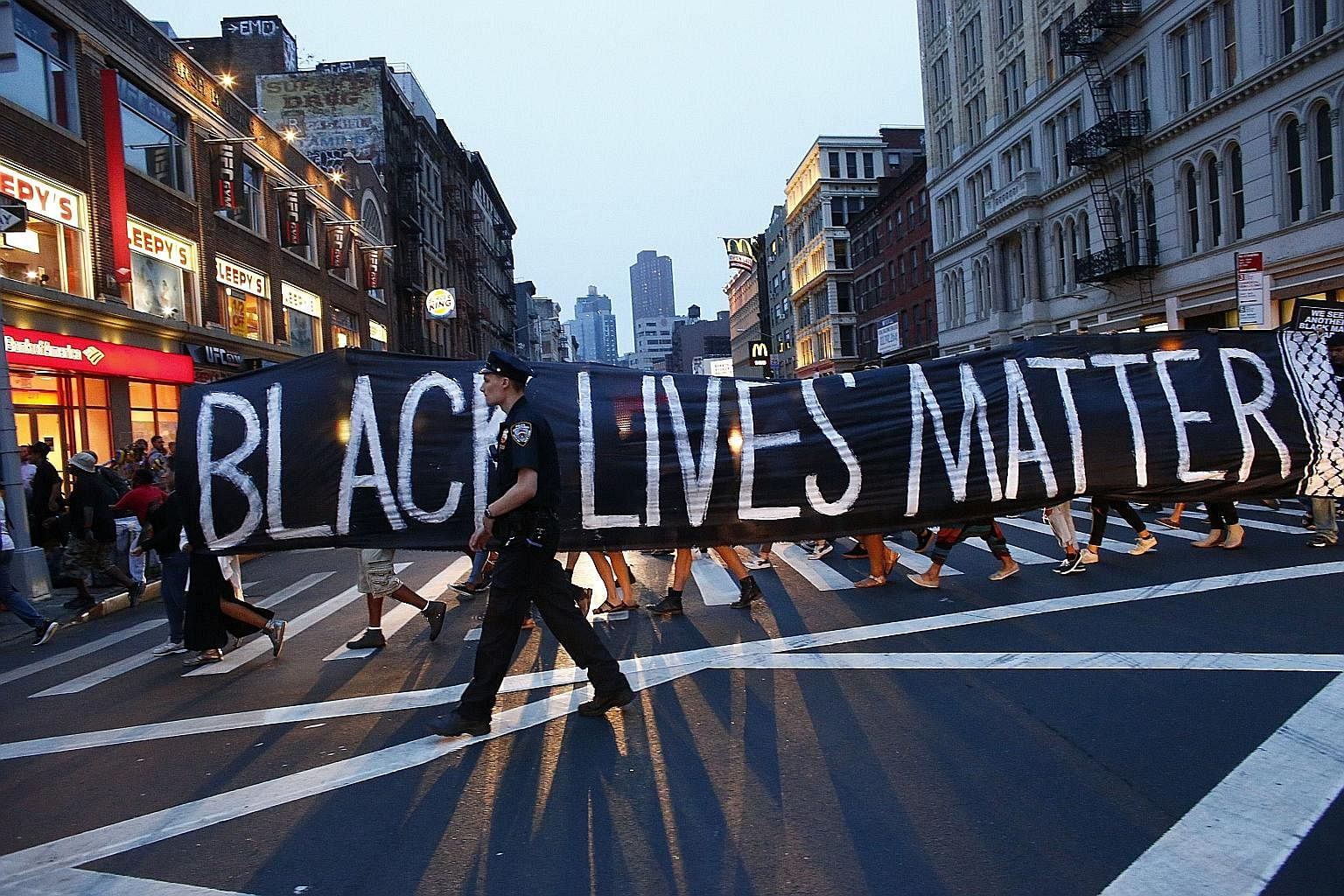 A police officer on patrol during a Black Lives Matter rally in New York last Saturday. Racial issues continue to divide Americans and amid the din of claims and counterclaims, saner voices are calling for a proper and real dialogue.