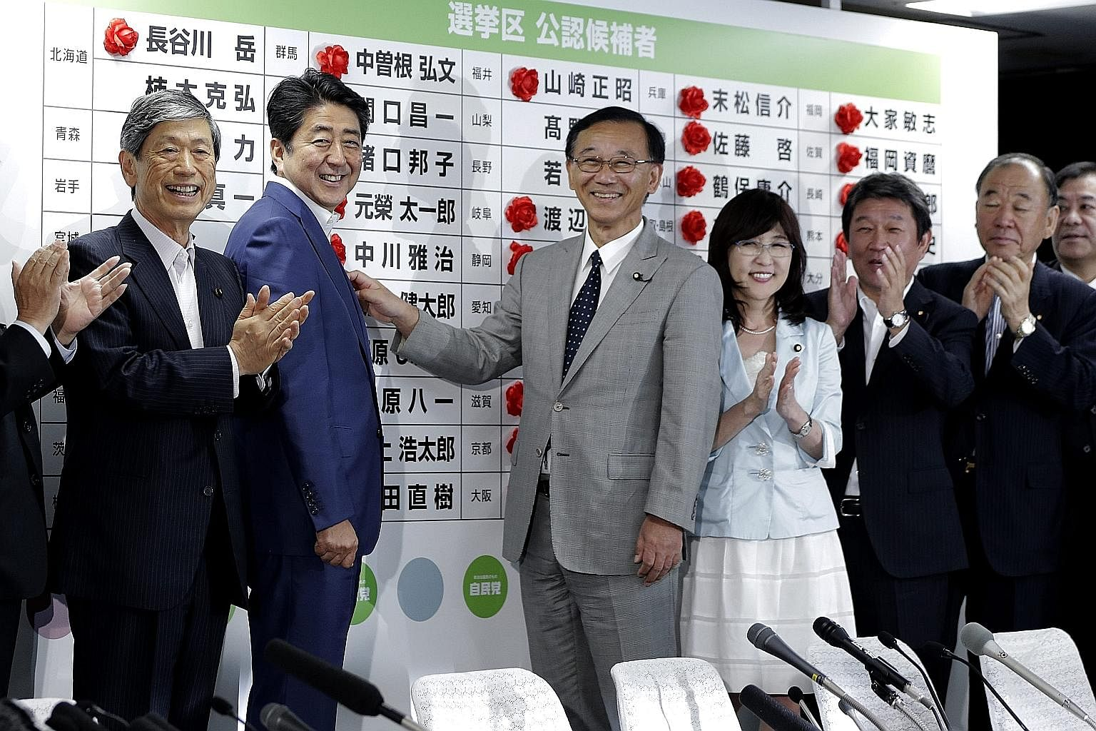 Japanese Prime Minister Shinzo Abe (second from left) celebrating with LDP members on Sunday at the party's headquarters in Tokyo after the Upper House election win. LDP and coalition partner Komeito now hold 146 of the 242 seats in the Upper House.