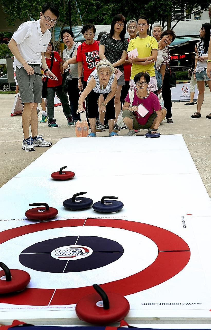 Madam Margaret Lee, 71, (squatting) and Madam Kok Ee San, 78, try out floor curling at a Community Sports Day event held yesterday. The sports day aims to promote racial harmony.