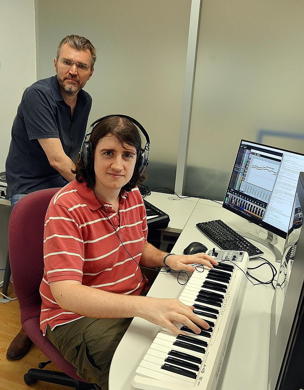 Dr Andrew Garner (in red) and Prof Vlatko Vedral at NUS' Centre for Quantum Technologies with a computer and keyboard set-up that translates quantum effects into musical sounds.
