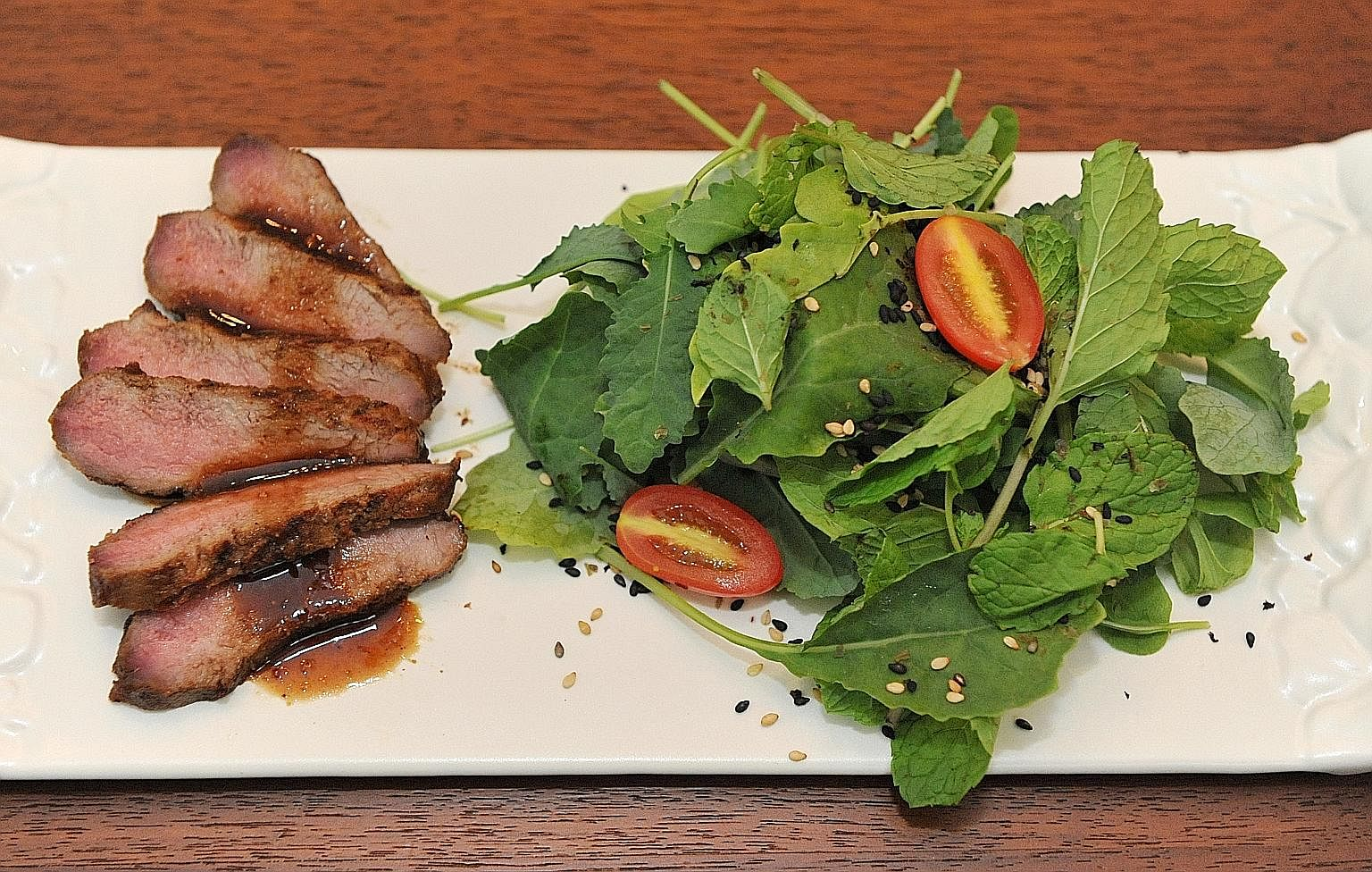 The grilled meat is served with bitter salad leaves to balance out the sweetness of the meat.