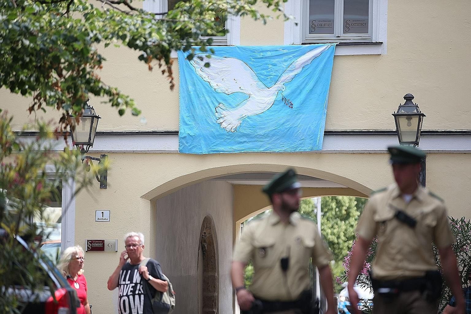 The man alleged to be Mohammad Daleel, the Syrian asylum seeker who detonated a bomb near the music festival in the German city of Ansbach. A banner depicting a peace dove in Ansbach, southern Germany, at the site where a Syrian blew himself up tryin