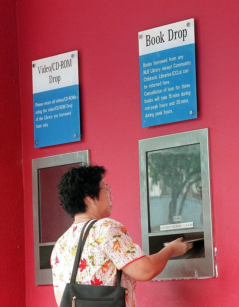 Library books being returned using a book drop. The National Library Board has other avenues to encourage prompt return of items, such as a free e-mail reminder service.