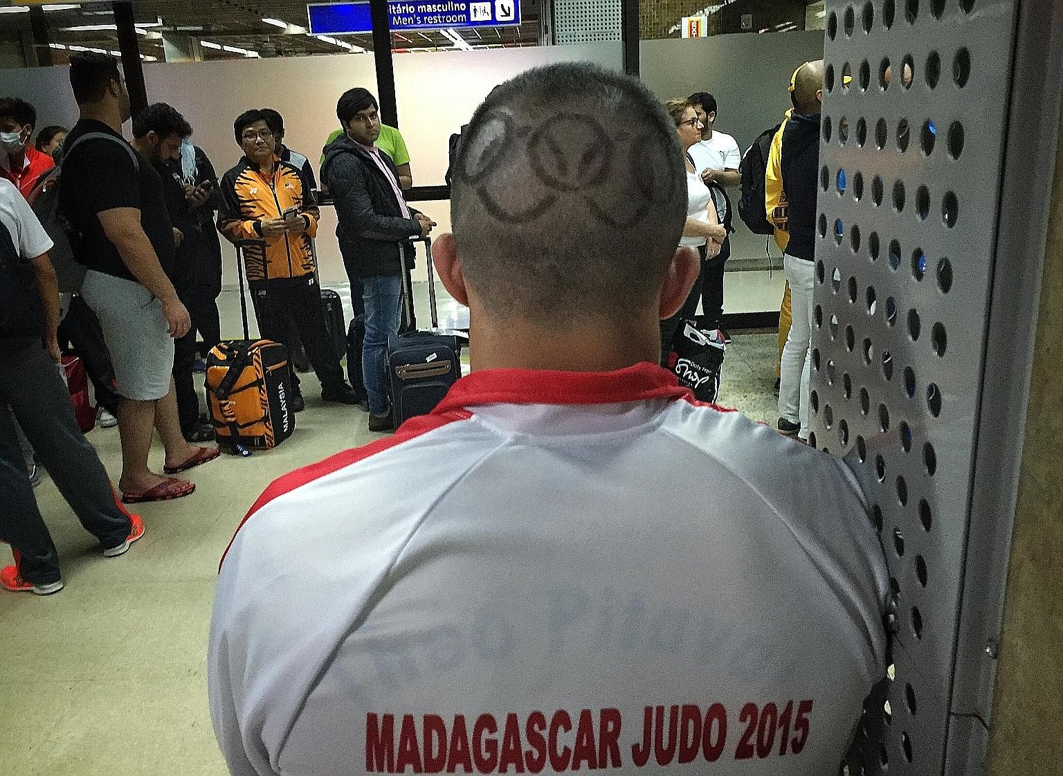 A Rio-bound Madagascar judo coach sports a haircut showing the Olympic logo as he waits in the boarding lounge at the Sao Paulo-Guarulhos International Airport.
