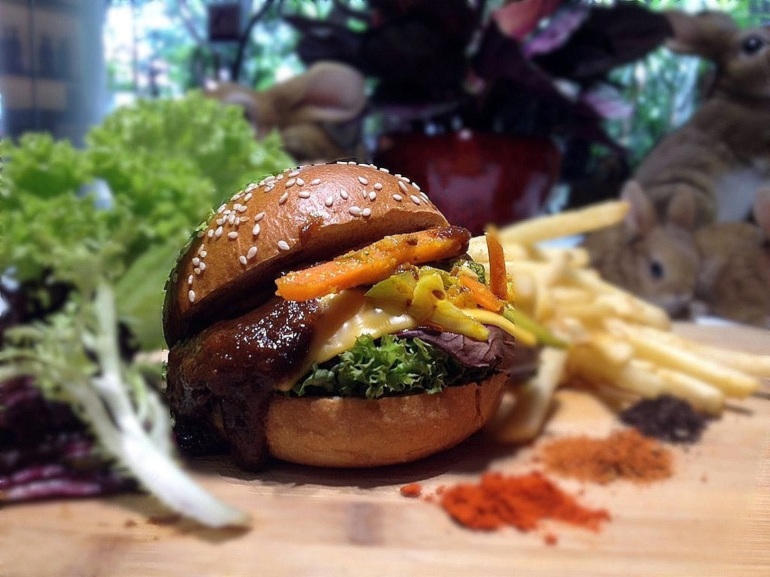 Beef cheek rendang burger with achar and Cajun fries (left) from Hareloom Cafe & Bar, run by chef Matthew Mok (above).
