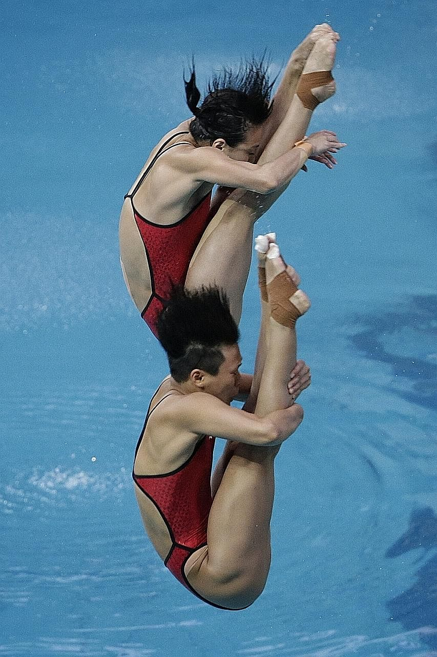 Wu Minxia (top) and Shi Tingmao during the women's synchronised 3m springboard event on Sunday. They led right through the five-round competition and won by a massive margin of 31.77 points.