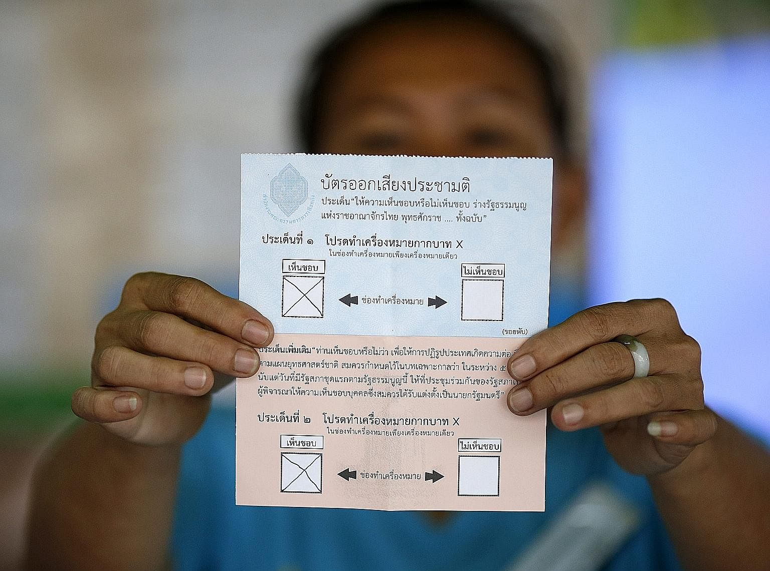 An election official shows a ballot paper in favour of Thailand's new draft charter. When adopted, this will be Thailand's 20th Constitution, and it will be harder to amend than the 2007 charter.
