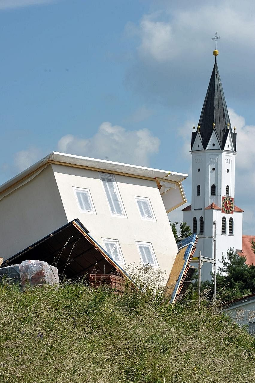 2 scale version of his home upside down in his garden to use as a shed. In doing so, he inadvertently created a tourist attraction in the town, about 80km from Munich in the southern state of Bavaria.