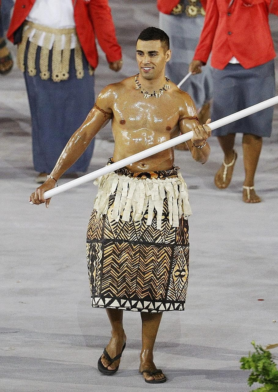 Tonga's flag bearer Pita Taufatofua (left) leading his contingent during the athletes' parade at the Olympics.