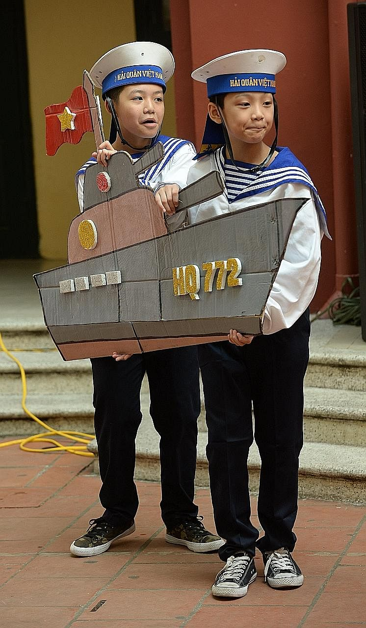 Two students, carrying a paper model of a navy ship, preparing to perform a dance in Hanoi yesterday, featuring the defence of Vietnam's islands in the South China Sea.