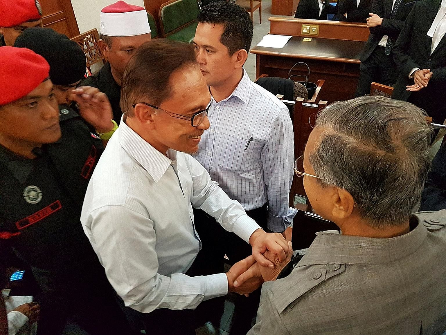 Malaysia's former prime minister, Dr Mahathir (right), shaking hands with Anwar at the Kuala Lumpur High Court on Monday - a gesture that led many to wonder if this could be the start of a new chapter in the country's politics.