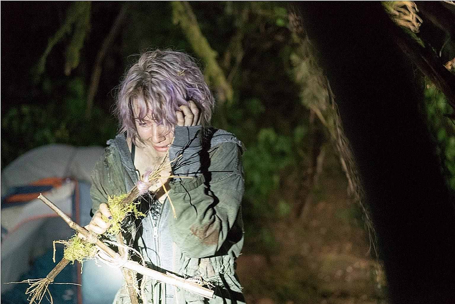 (Above) Valorie Curry in the Blair Witch reboot, which is based on the invented history of an 18th-century woman cast out and left to die in the Maryland woods.
