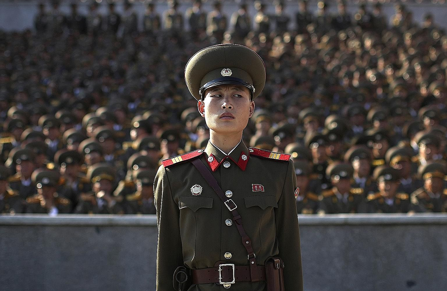 """A soldier at a parade in Pyongyang, North Korea, on Oct 10 last year to mark the 70th anniversary of the country's ruling party. A photographer making an """"official"""" group picture, using an 8x10 camera, of the """"educated youth"""" of the Youth Shock Briga"""