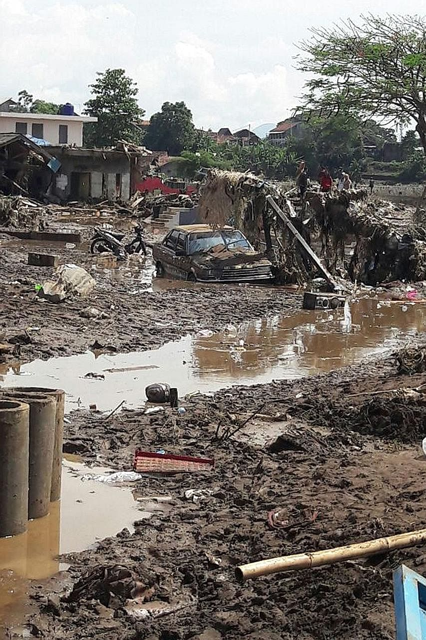 Vehicles and buildings were damaged in Garut, in Java, as the area was hit by flash floods after torrential rain on Tuesday. Military staff and volunteers helped to evacuate about 1,000 residents.