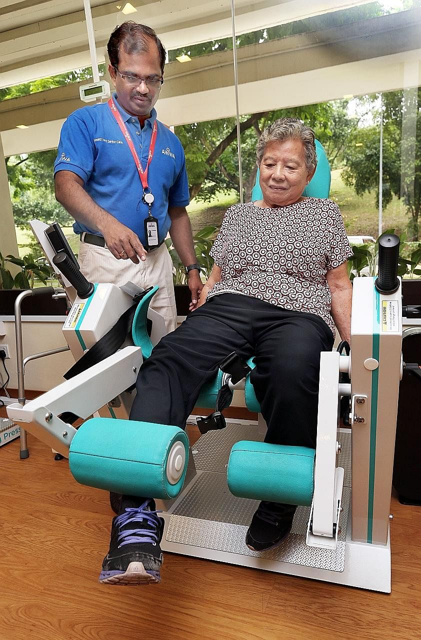 Madam Ooi using a Gym Tonic machine with help from senior occupational therapist P. Pandiarajan. She no longer suffers knee pain and can go to the wet market by herself.