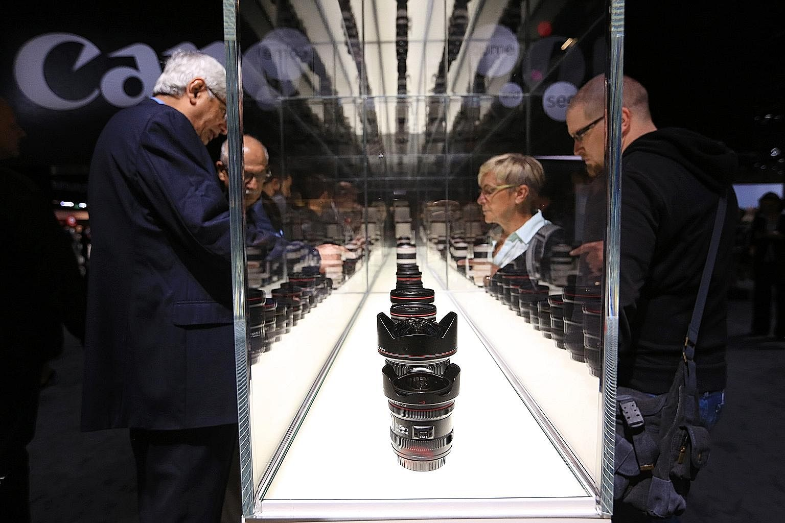 Visitors browsing a display containing a selection of Canon camera lenses during the Photokina photography trade fair in Cologne on Sept 20. At the Photokina photography trade fair, Sony unveileda the the a99 II, the long-awaited successor to