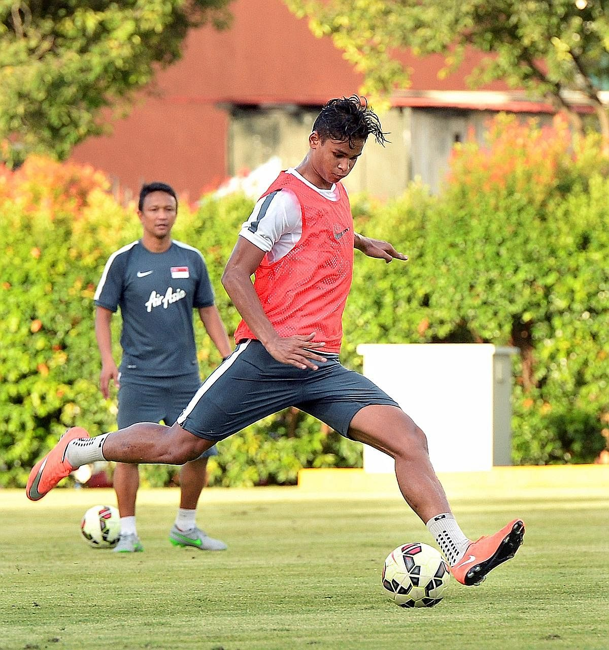 Irfan Fandi shaping to shoot during his first training session with the senior national team in March as his father Fandi Ahmad watches on at the Geylang Field. The 19-year-old may receive his first senior cap against Malaysia next week.