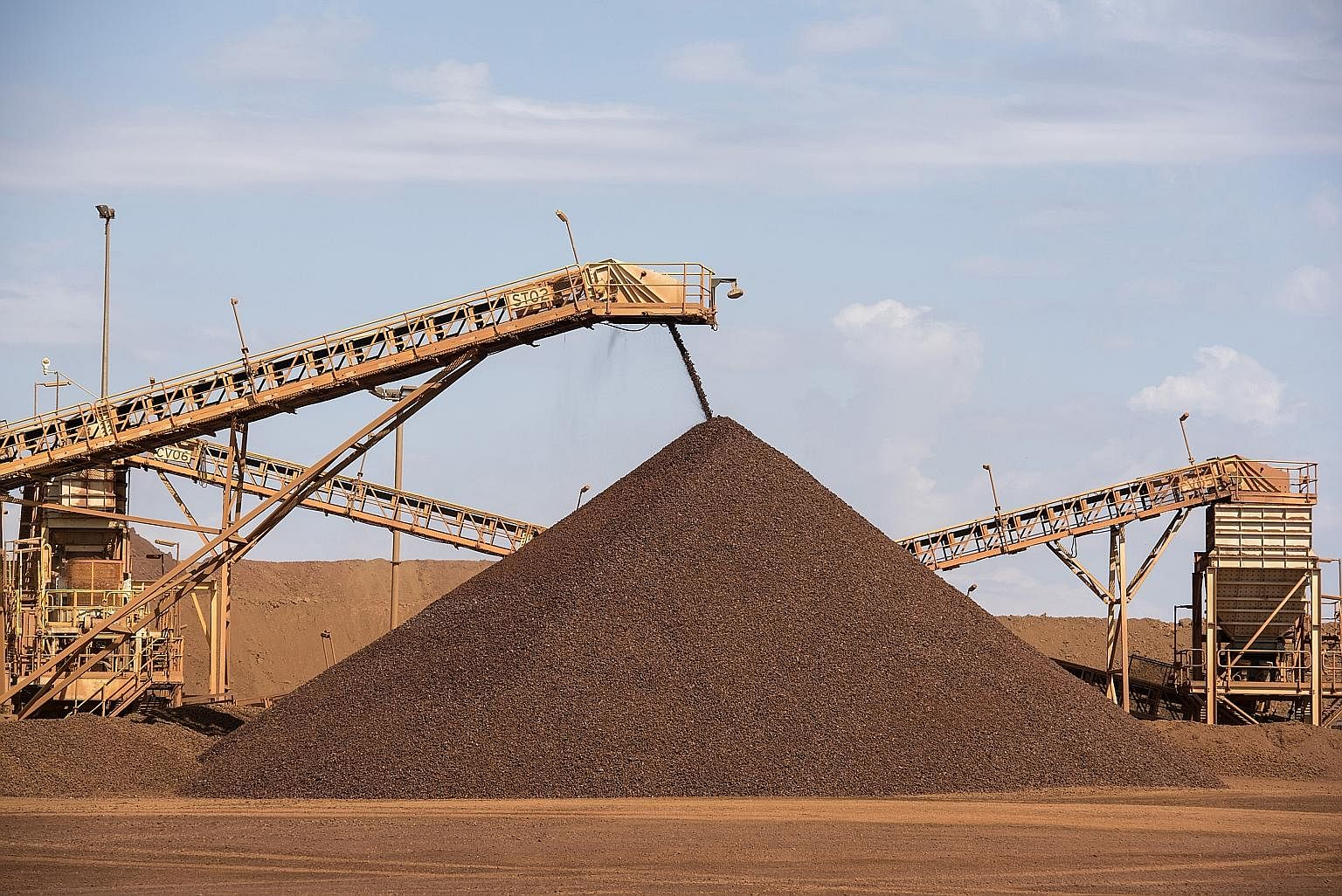 Fragmenting rock by blasting in an iron ore mine in Western Australia; the ore waiting to be scooped up and transported; enormous trucks delivering iron ore to Port Hedland, a sleepy backwater which became one of the biggest ports in the wo