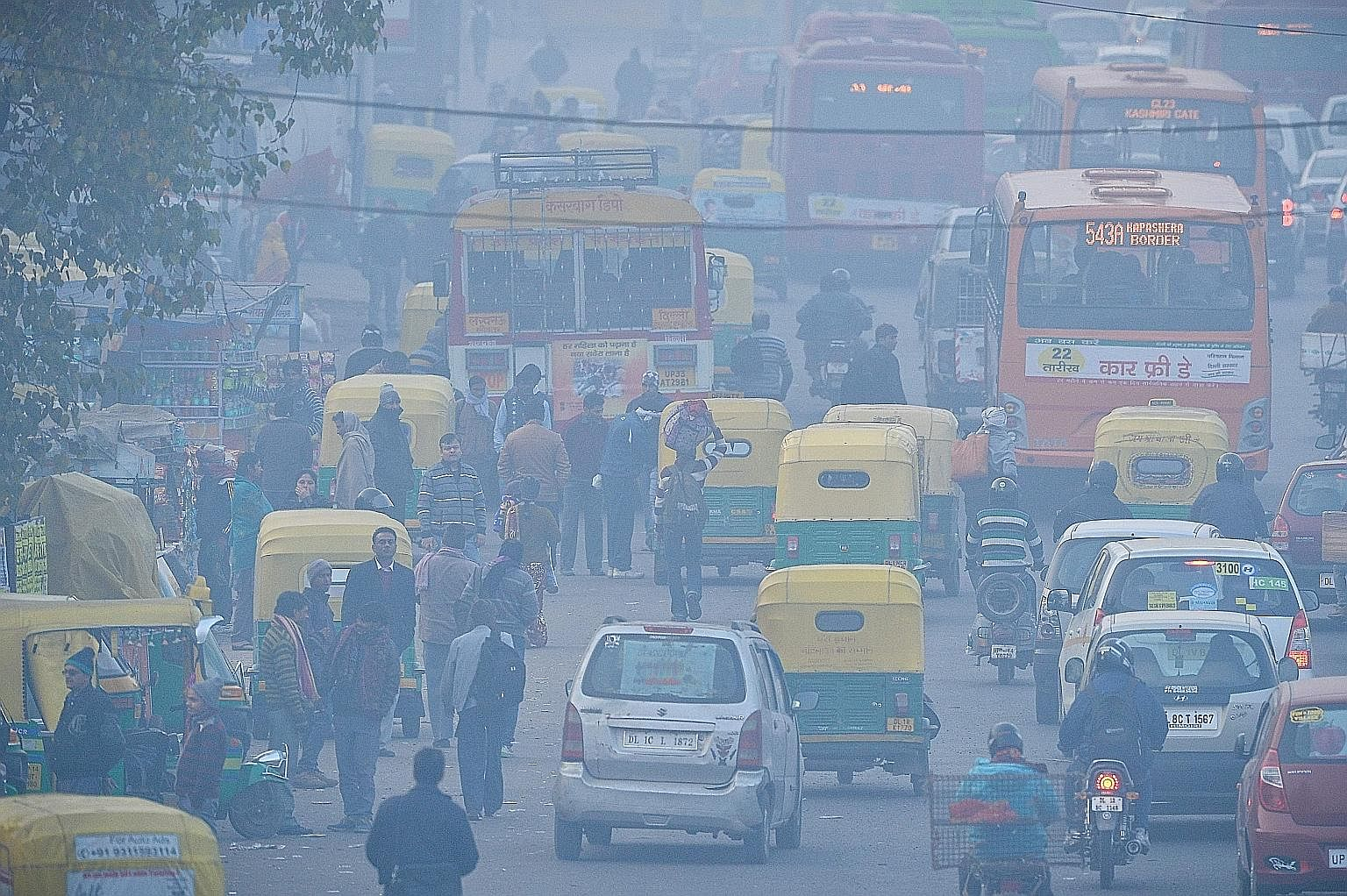 Commuters travelling on a polluted road near a bus terminus in New Delhi.
