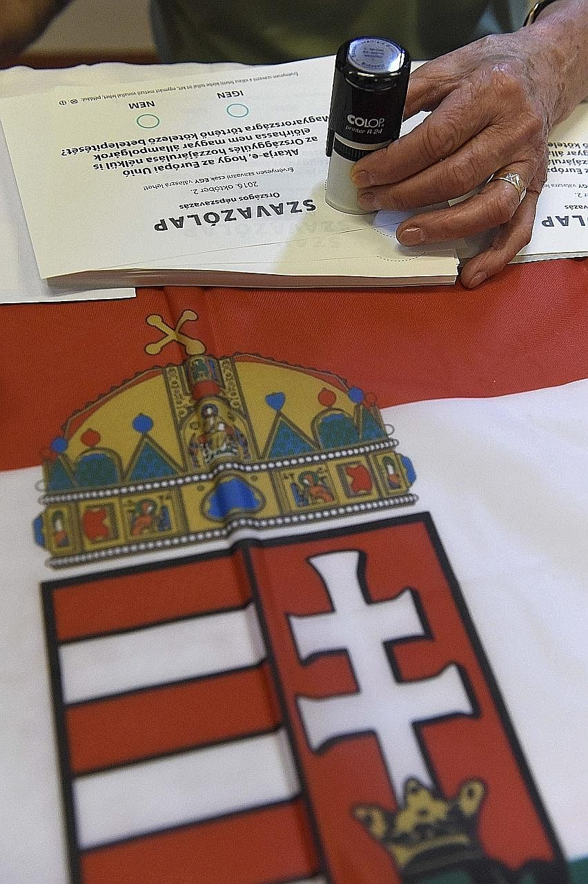 Ballot papers being stamped atop the national flag as Hungarians cast their votes at a polling station in Budapest yesterday. If the turnout falls below 50 per cent, the referendum could be deemed invalid.