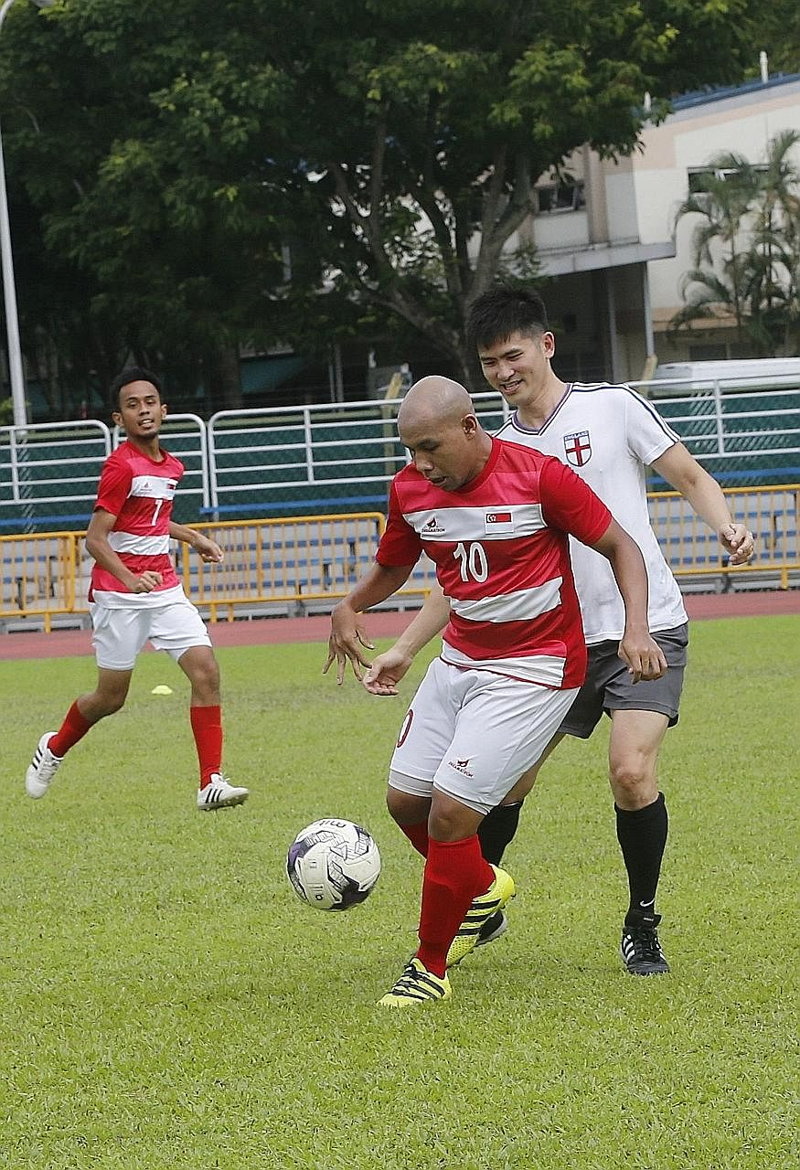 Singapore's national cerebral palsy football captain Khairul Anwar shielding the ball from a player from the Hwa Chong Institution alumni team in a friendly match at Queenstown Stadium yesterday. The Hwa Chong alumni team won 7-2. Singapore CP footba