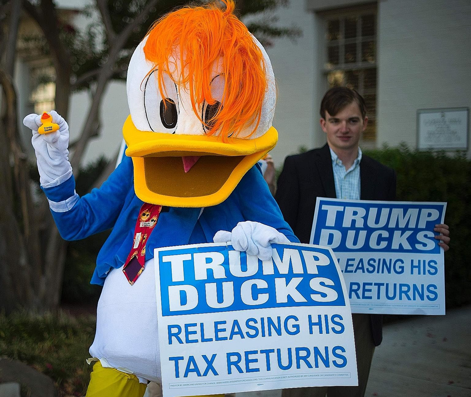 """A protester dressed as Donald Duck protesting against Republican presidential nominee Donald Trump, who told his opponent Hillary Clinton in the first presidential debate that paying no federal income taxes made him """"smart"""". When the wealthy avoid pa"""