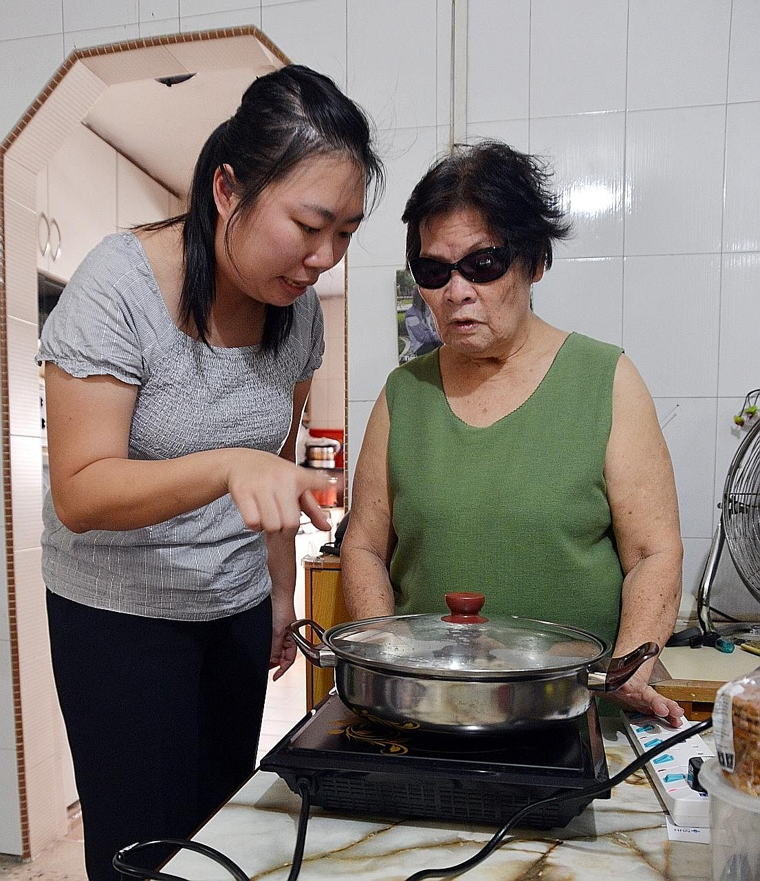Senior occupational therapist Chen Xuanyu shows housewife Joy Leong how to cook food and boil water more safely. Madam Leong has total vision loss in one eye and partial vision in the other.