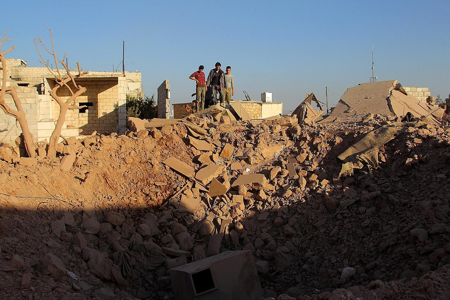 People inspecting an air strike's aftermath in the Syrian rebel-held village of Owaijel on Monday. In addition to military operations in the Middle East, the US must direct foreign policy in the middle of a markedly bitter election.