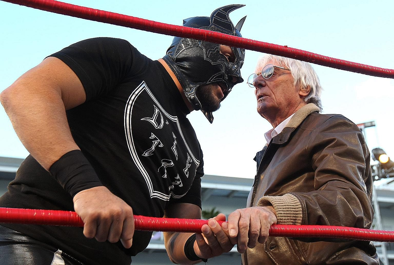 Formula One commercial boss Bernie Ecclestone talking to a wrestler in Mexico City on Thursday, before the Mexican Grand Prix weekend kicked off. Ecclestone had to wrestle with a few issues of his own before the recent US$4.4 billion (S$6.13 billion)