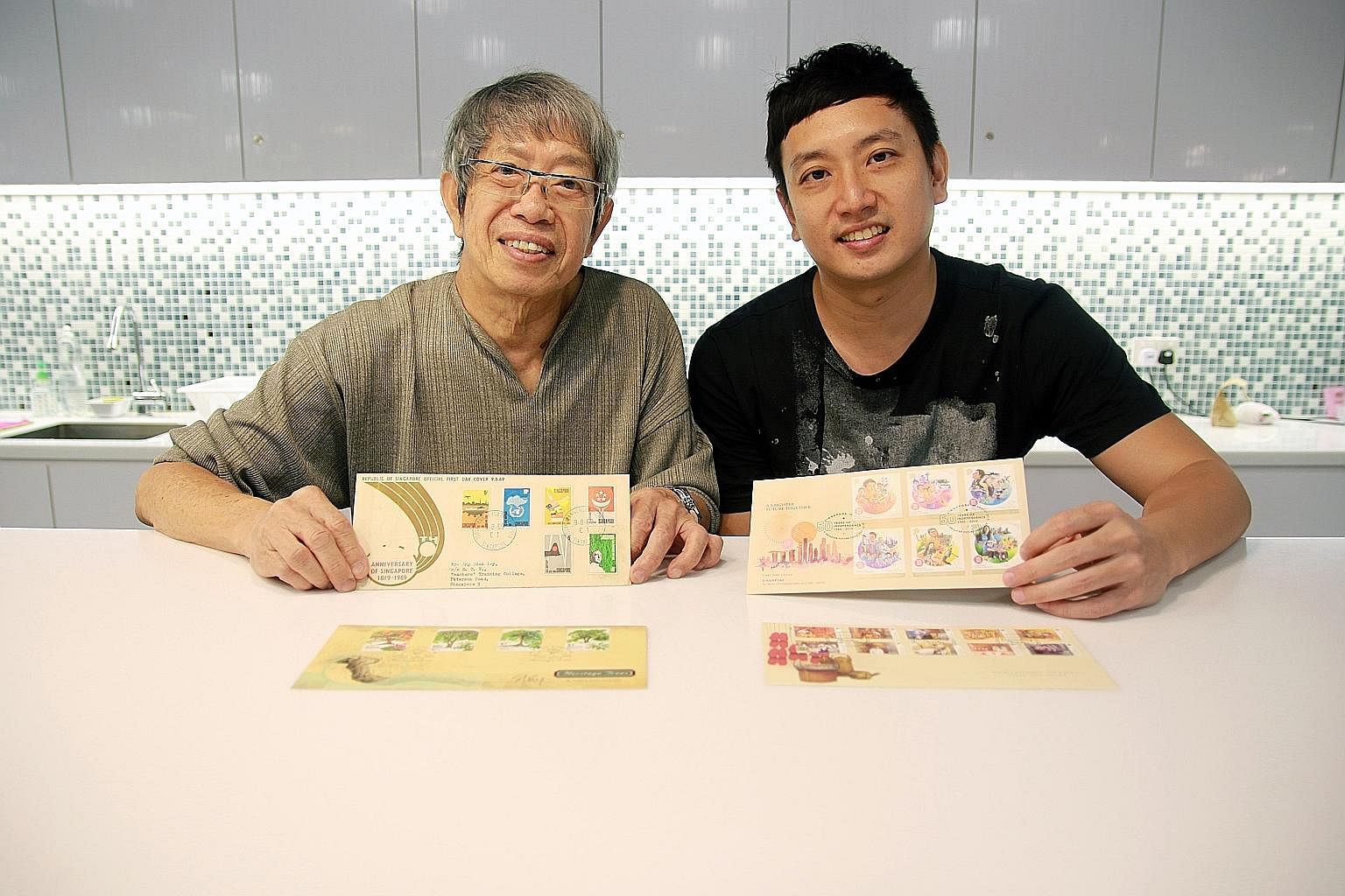 Mr Eng Siak Loy, Singapore's longest-serving stamp designer, and his son Tze Ngan.
