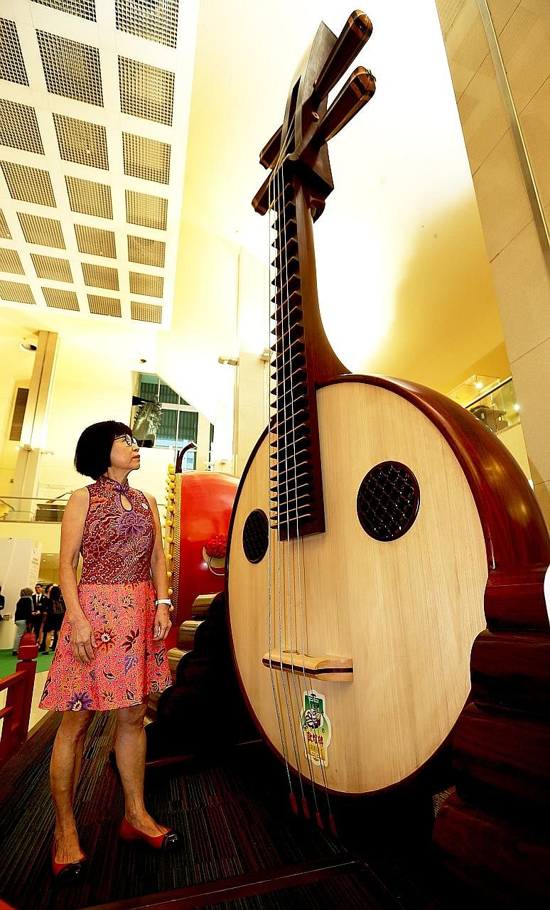 Ms Chek with a 4.6m-tall ruan weighing 702kg at the foyer of the Singapore Conference Hall, where a giant erhu and guzheng are also on display - part of an exhibition marking two decades of the Singapore Chinese Orchestra.