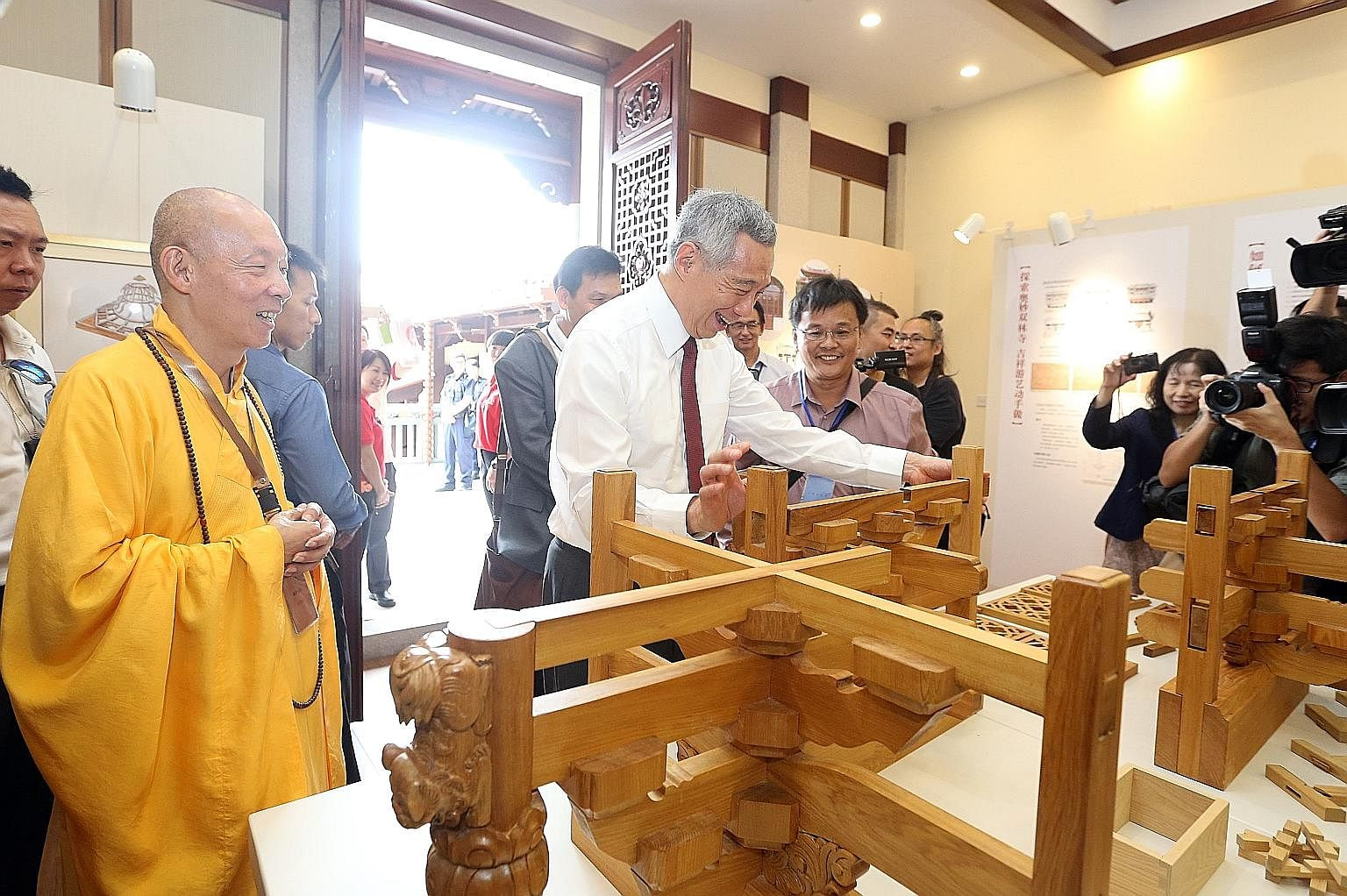 The Meditation Hall is among the new halls added in the $20 million second phase of the Lian Shan Shuang Lin Monastery's restoration programme. Left: PM Lee trying out the wooden structures in the Dharma Hall at the monastery in Kim Keat yeste