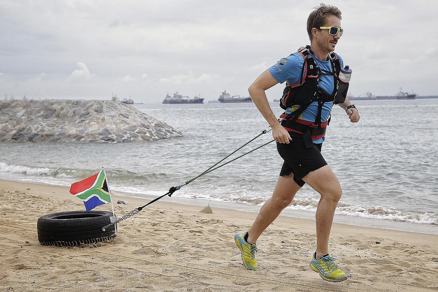 Jethro De Decker running on the beach with a 10kg tyre strapped to his body at East Coast Park yesterday. He will take part in the Standard Chartered Marathon Singapore next month as part of his training to trek from Antarctica to the South Pole on h