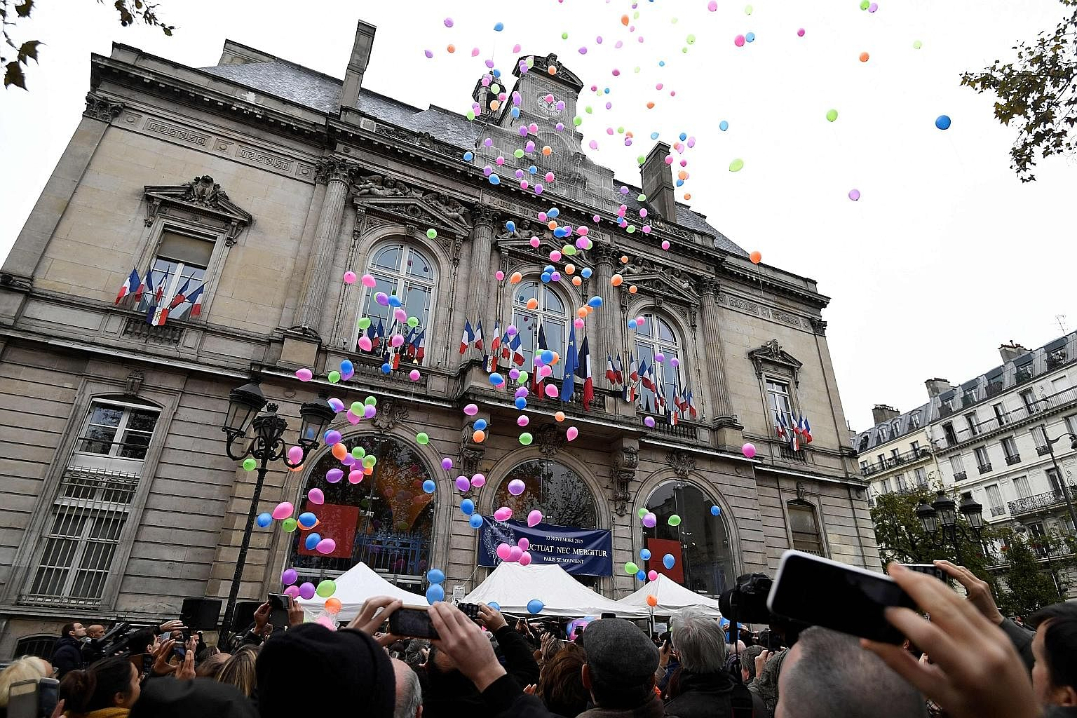 To mark the first anniversary of the Nov 13 terrorist attacks in Paris, people released balloons (above) in front of the city hall of Paris' 11th arrondissement yesterday while Sting (below) played a day earlier at the reopening of the Bataclan conce