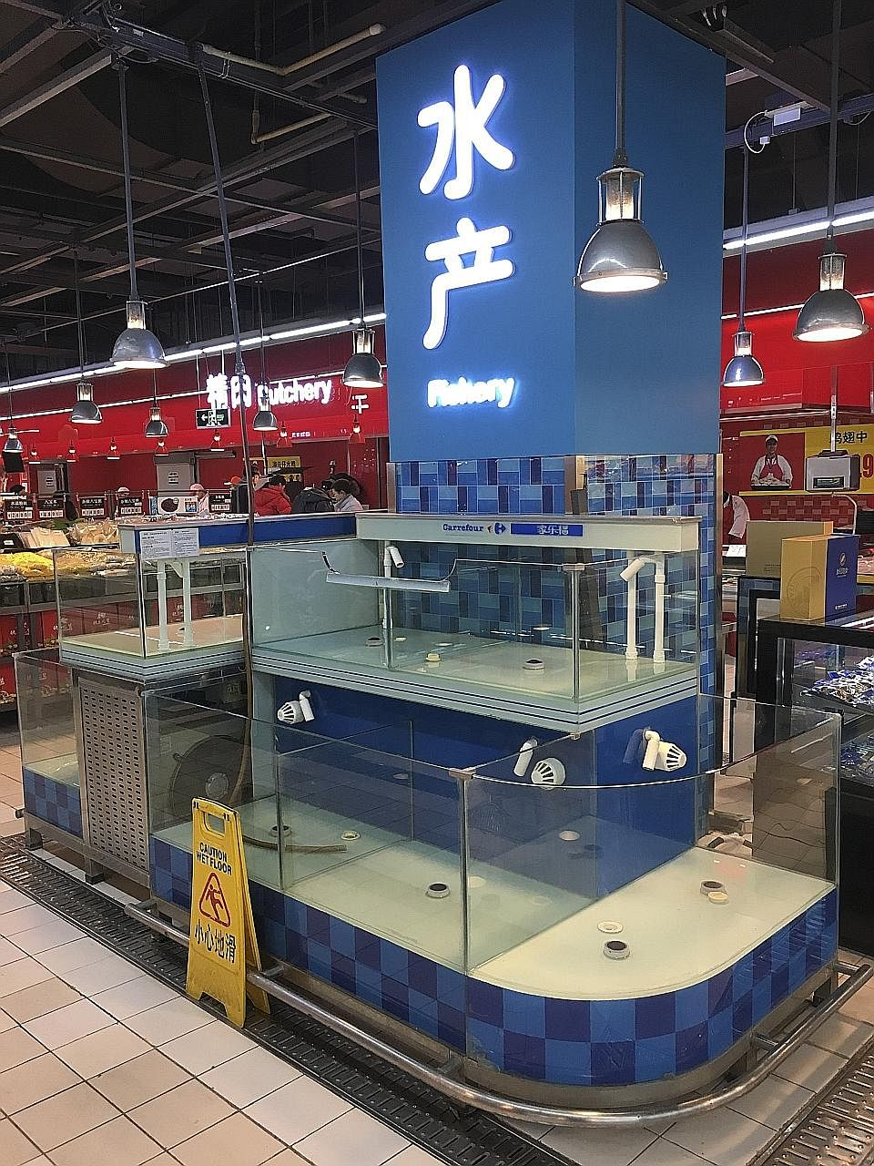 Tanks that normally hold freshwater fish left empty in a Carrefour supermarket in Beijing on Thursday. Not all supermarkets in the city have removed their live fish, but fish in many other stores are gone with no explanation.