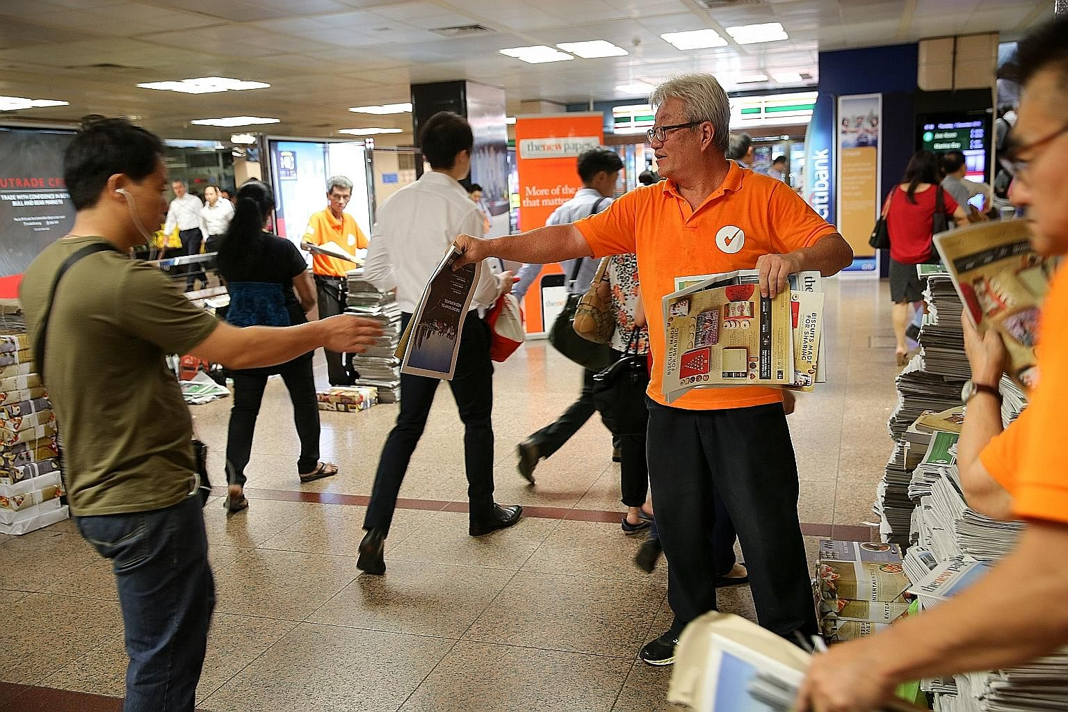 A commuter grabbing a TNP copy at Raffles Place MRT station, one of the regular poi