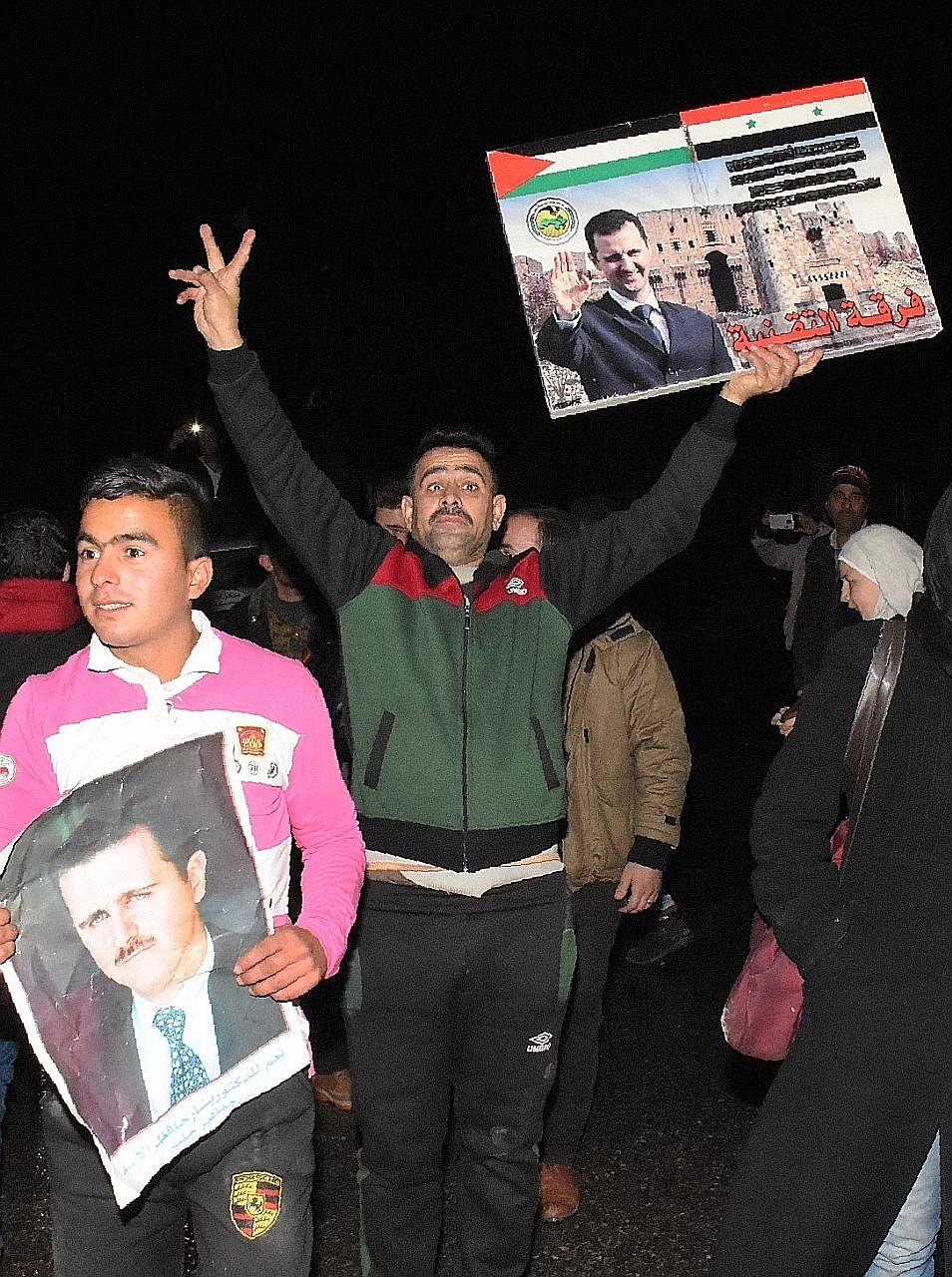 A man displaying a placard with Mr Assad's portrait as people thronged the streets in Aleppo on Thursday.