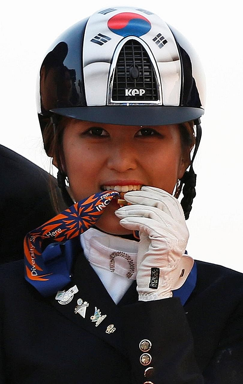 Ms Chung in a 2014 photo after winning an Asian Games gold medal in an equestrian event. Samsung Electronics' sponsorship of her riding career is an element of the investigation into her mother Choi Soon Sil's involvement in an influence- peddling sc