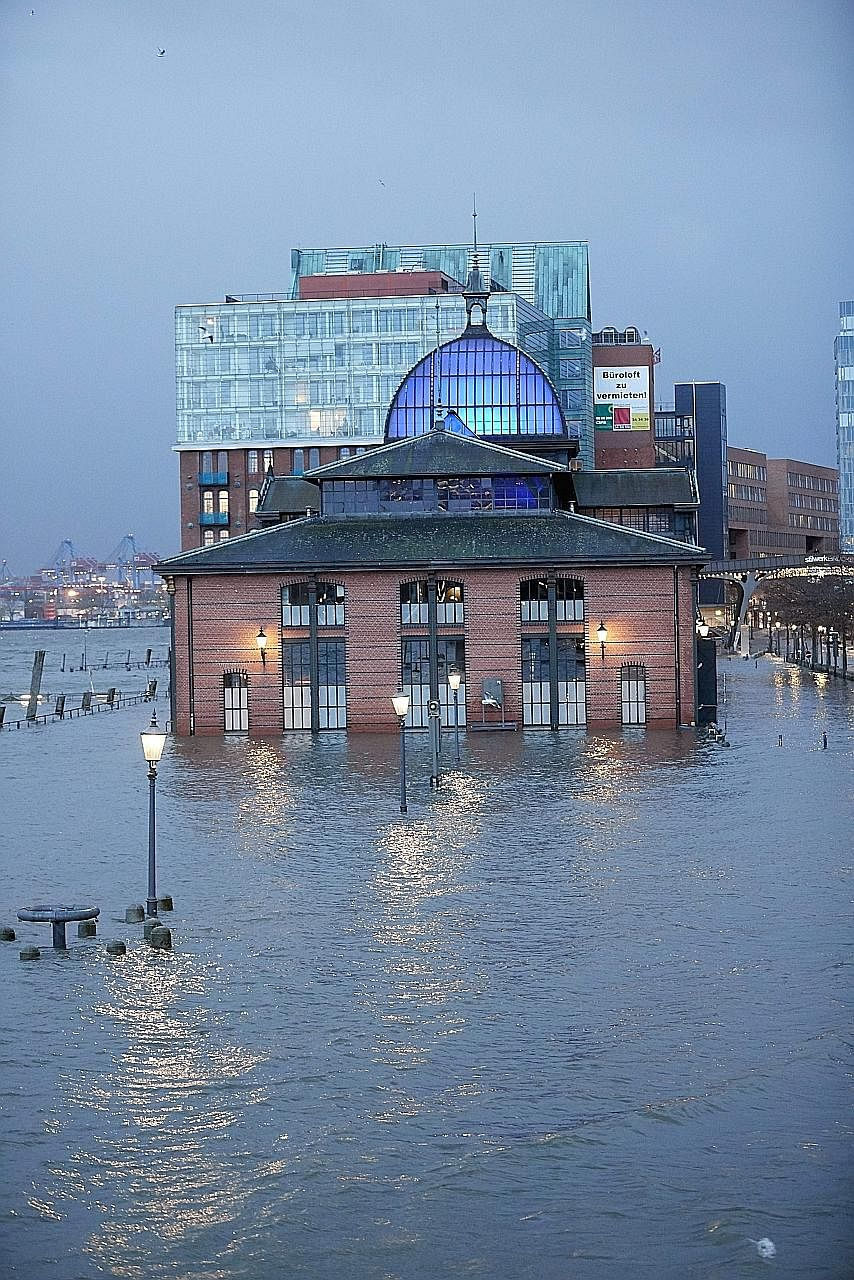 The historic Fish Auction Hall in Hamburg was immersed in knee-deep waters yesterday as the storm brought heavy winds, flooding and snowfall across the country.