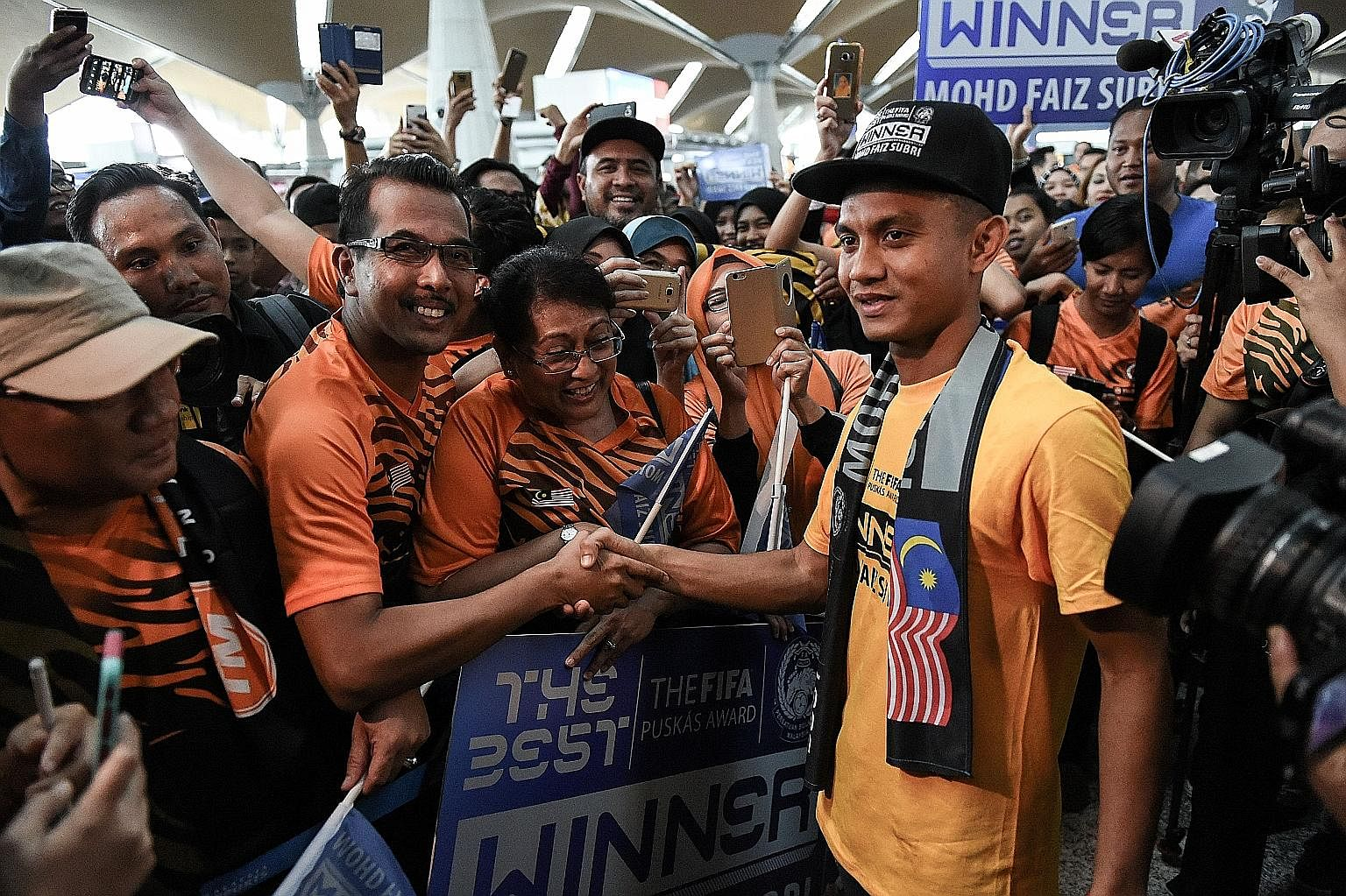 Malaysian footballer Mohd Faiz Subri (right) greeting supporters at the Kuala Lumpur International Airport after winning the Puskas Award The 29-year-old Penang forward has never started for his national team.