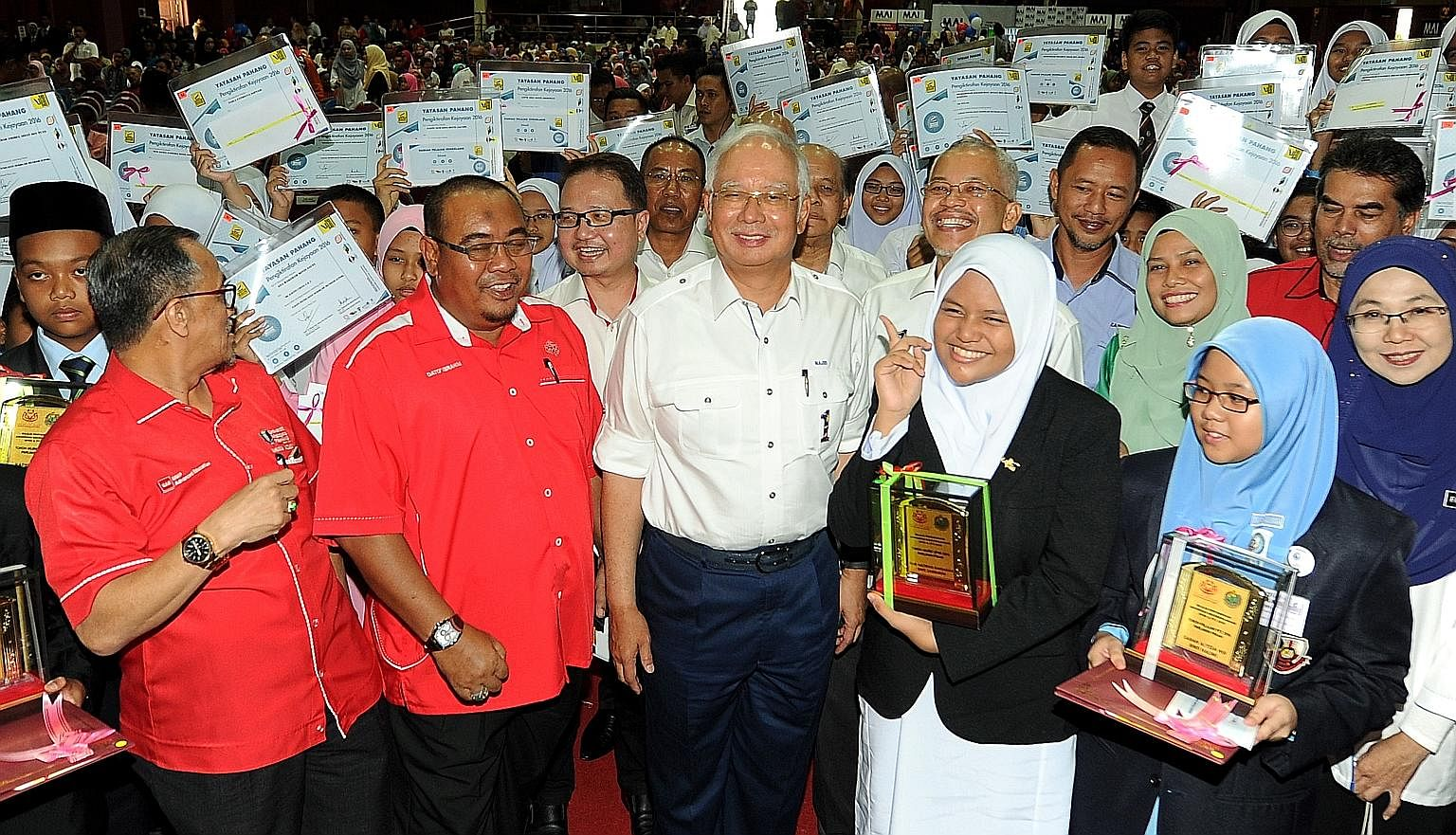 Mr Najib Razak (centre), seen here at an event in Pahang yesterday, criticised his predecessor Mahathir Mohamad for saying the opposition would continue giving cash handouts after criticising the aid programme earlier.