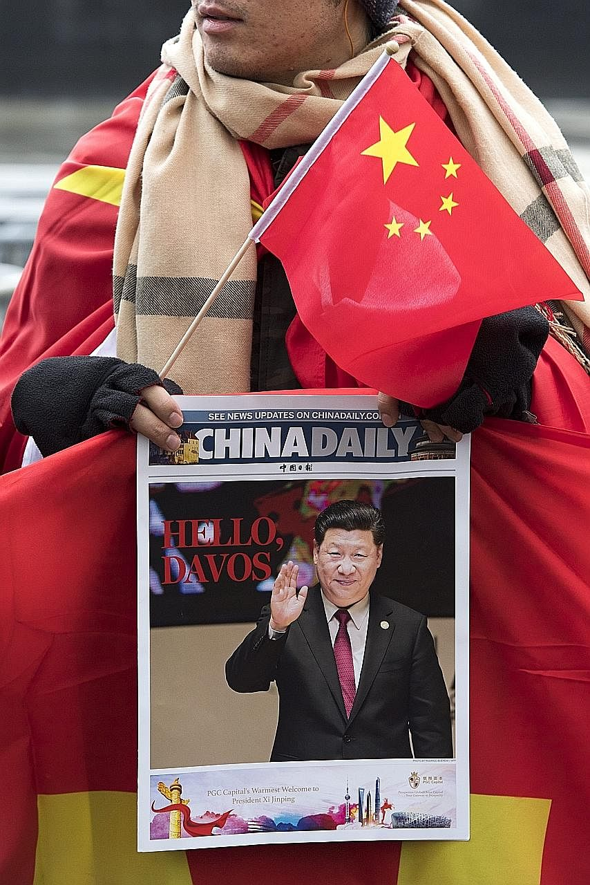 With a Chinese flag and the China Daily in hand, a supporter waits outside the Parliament building in Bern for Mr Xi. The Chinese leader will deliver a keynote speech in Davos today.