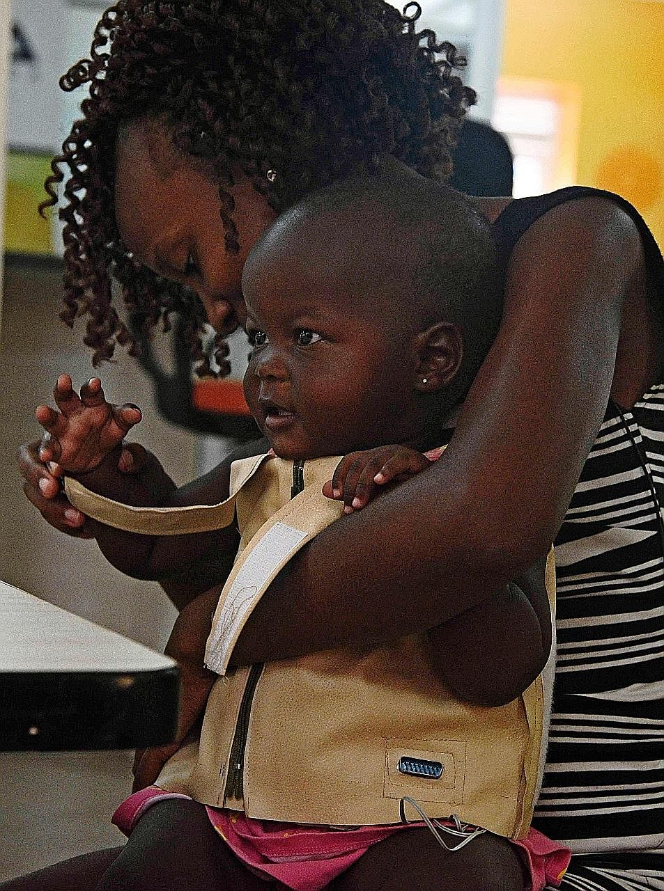 A child being fitted with a Mama-Ope jacket at Uganda's Makerere University School of Public Health.