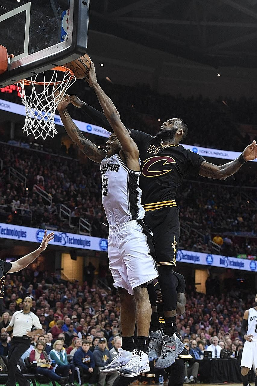LeBron James of the Cleveland Cavaliers (right) attempting to block Kawhi Leonard of the San Antonio Spurs during overtime at the Quicken Loans Arena in Cleveland, Ohio on Saturday. The Spurs defeated the Cavaliers 118-115.