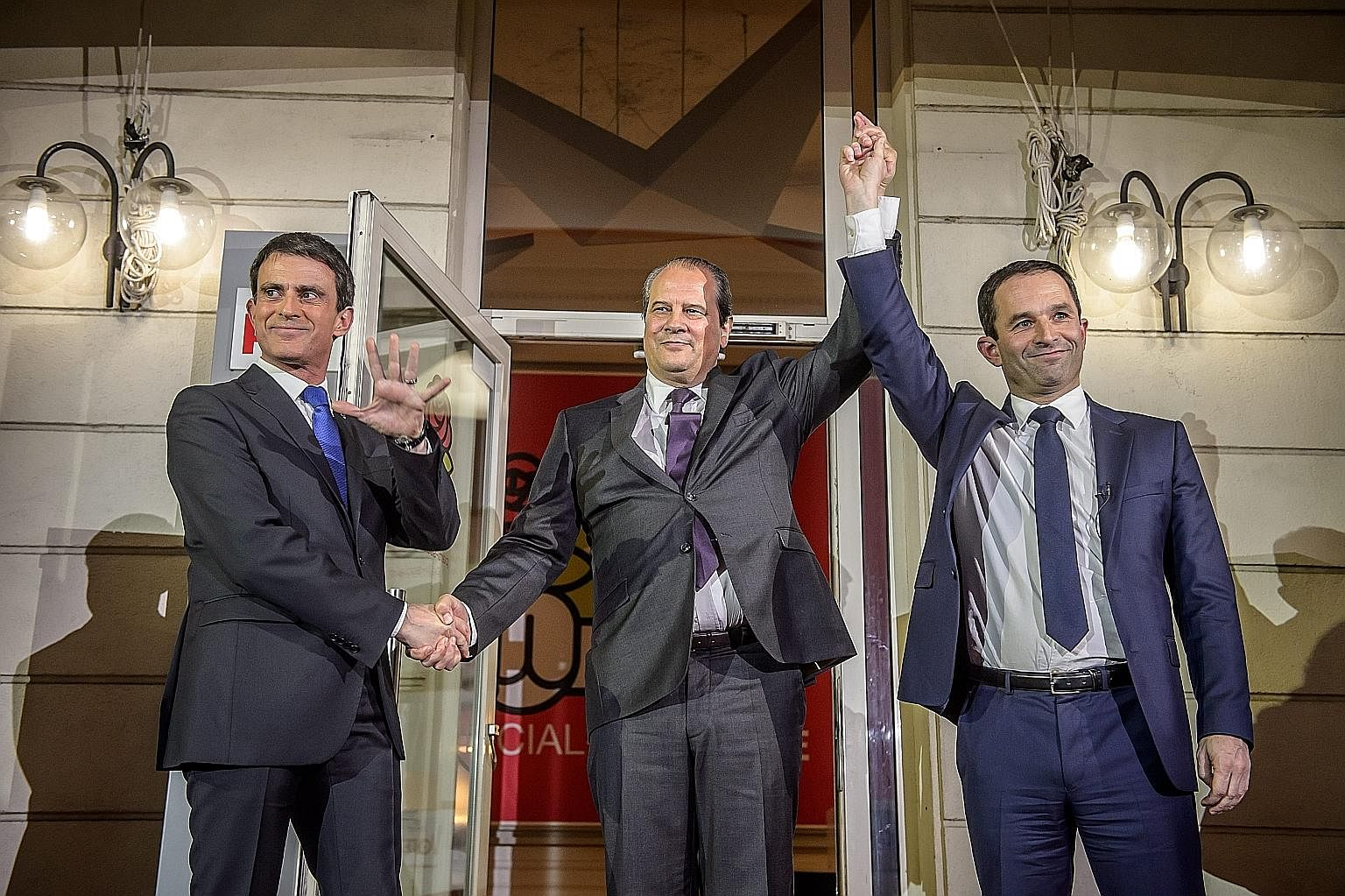 French Socialist party secretary Jean-Christophe Cambadelis (centre) flanked by Mr Benoit Hamon (far right), the winner of the second round of the party's primaries for the 2017 presidential election, and his opponent Manuel Valls on Sunday.