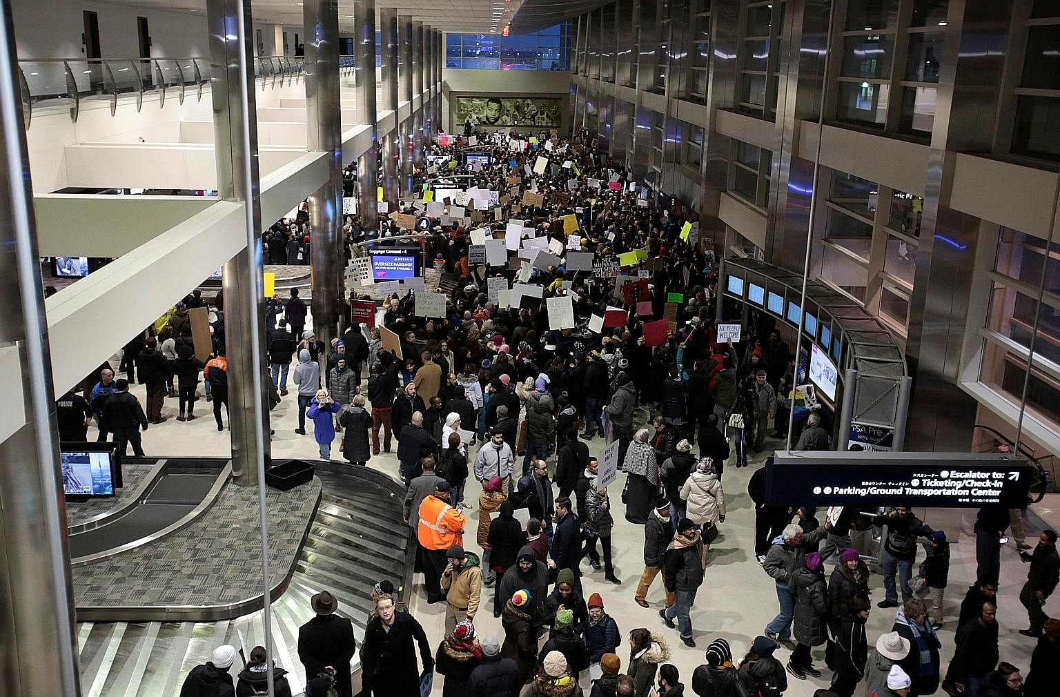 Volunteer lawyers setting up camp at Chicago's O'Hare Airport on Sunday to help immigrant travellers and their families after Mr Trump issued an executive order on immigration. Protesters gathering at the baggage claim area of Detroit Metropolitan Ai