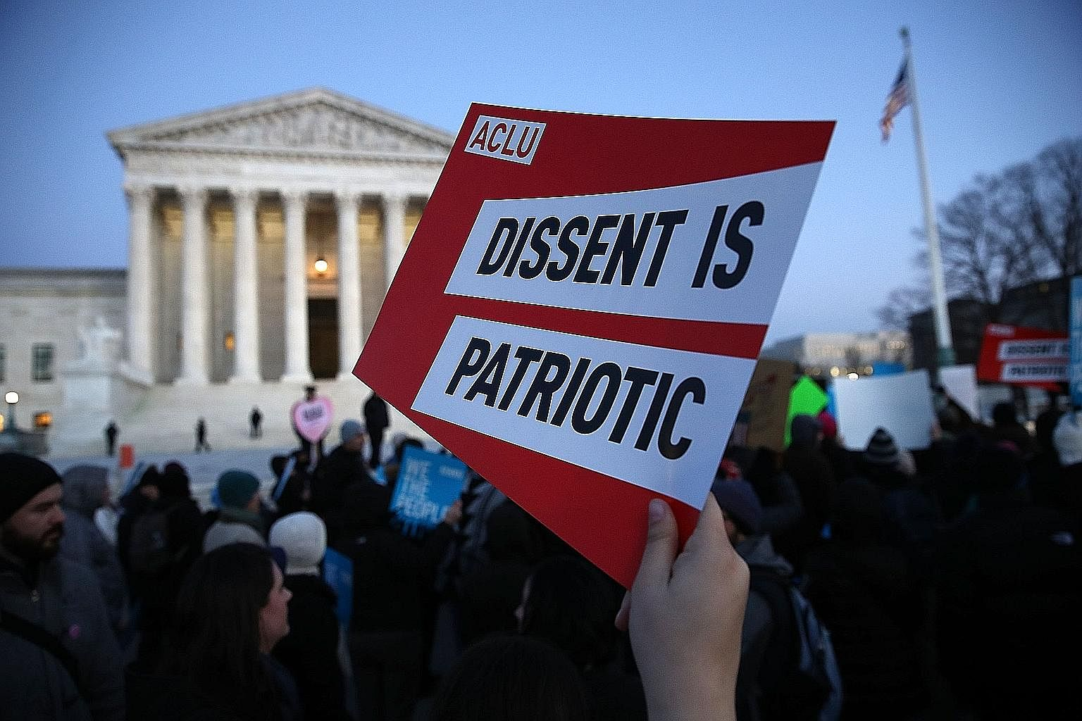 Protesters demonstrating outside the Supreme Court on Monday against US President Donald Trump's recent executive order that suspends the processing of all visa applications for people from seven Muslim-majority nations and temporarily halts America'
