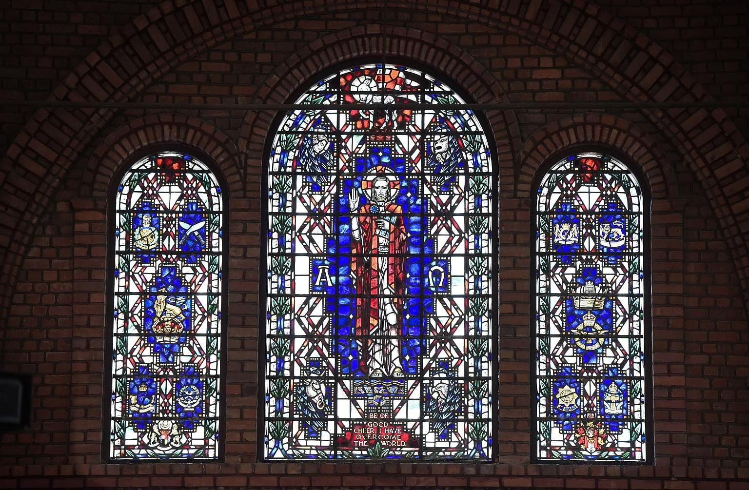 Stained glass windows bearing the image of Christ and the badges of the various regiments and forces that fought for the British in Malaya and Singapore.